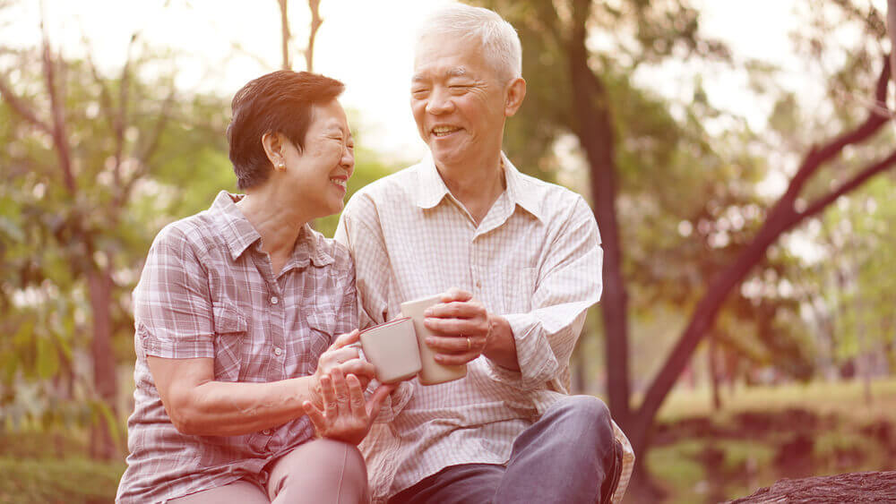 Older Japanese couple sharing tea together in nature