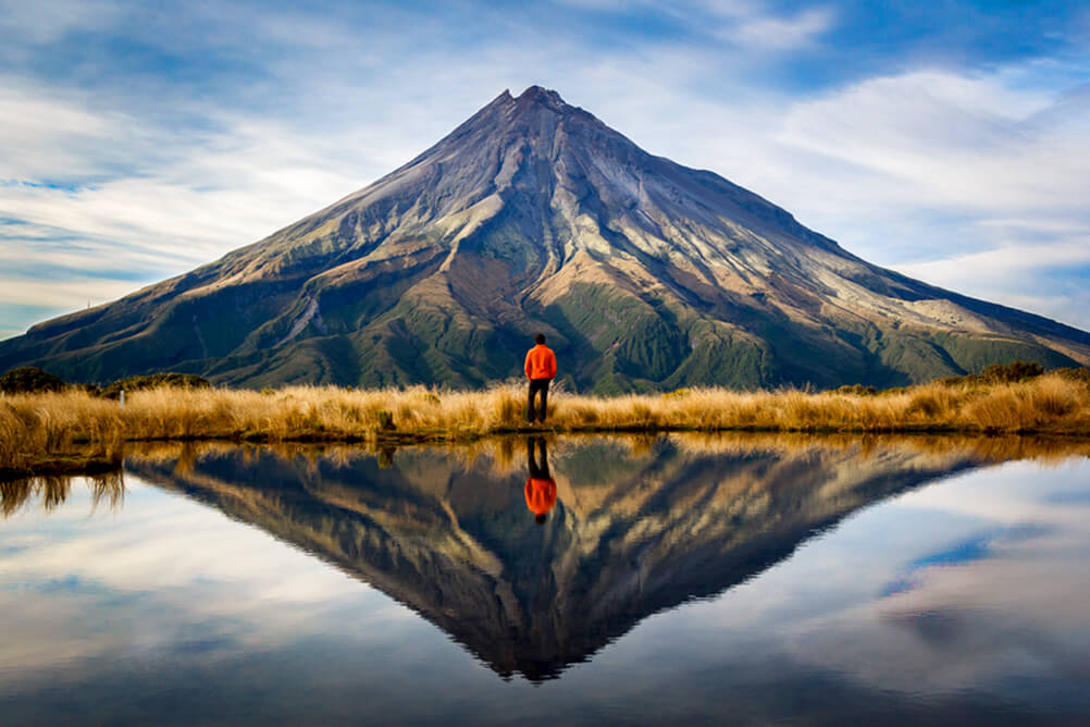 Man stands facing a mountain, reflected in a clear lake