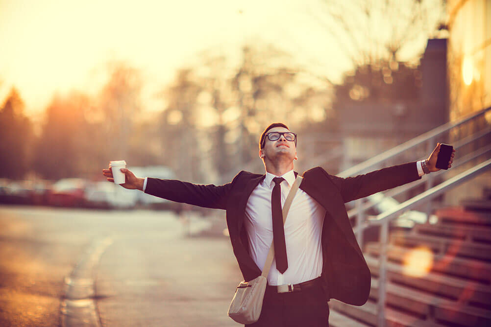 A man in a suit spreads his arms in joy after finding a winning lottery ticket on the street